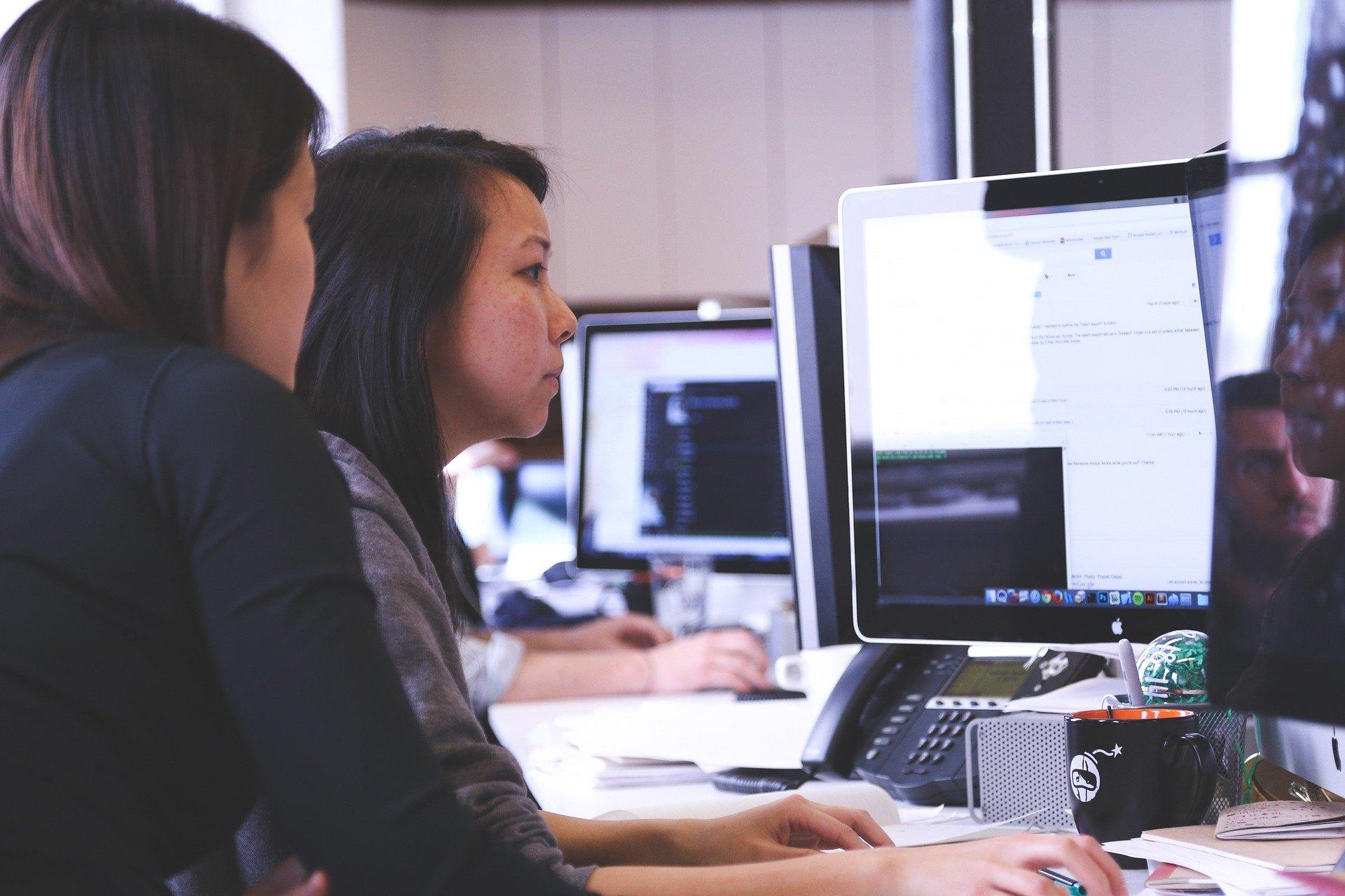 Das Foto zeigt zwei Frauen von der Seite. Sie sitzen vor einem Laptop. Im Hintergrund sind weitere Bildschirme zu sehen.