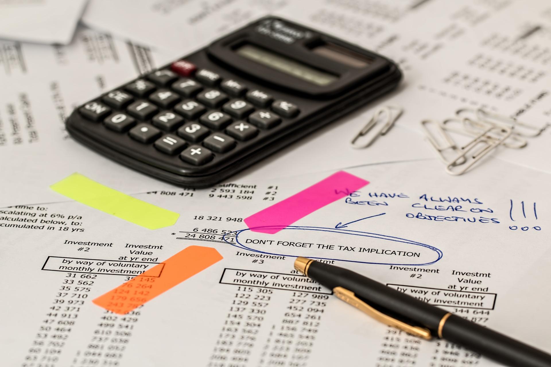 Das Foto zeigt ein Blatt Papier mit verschiedenen Zahlenbudgets. Darauf liegen ein Taschenrechner und ein Stift.
