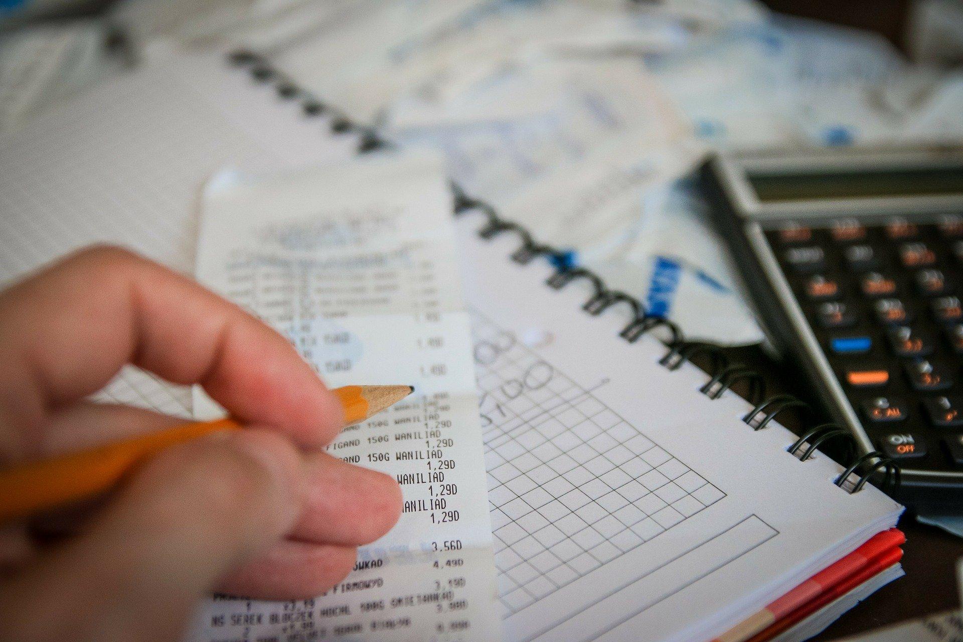 Das Foto zeigt einen Notizblock, rechts daneben ein Taschenrechner. Auf dem Notizblick liegt eine Quittung. Eine Hand, die einen Bleistift hält, geht die Positionen, die auf der Quittung vermerkt sind, durch.
