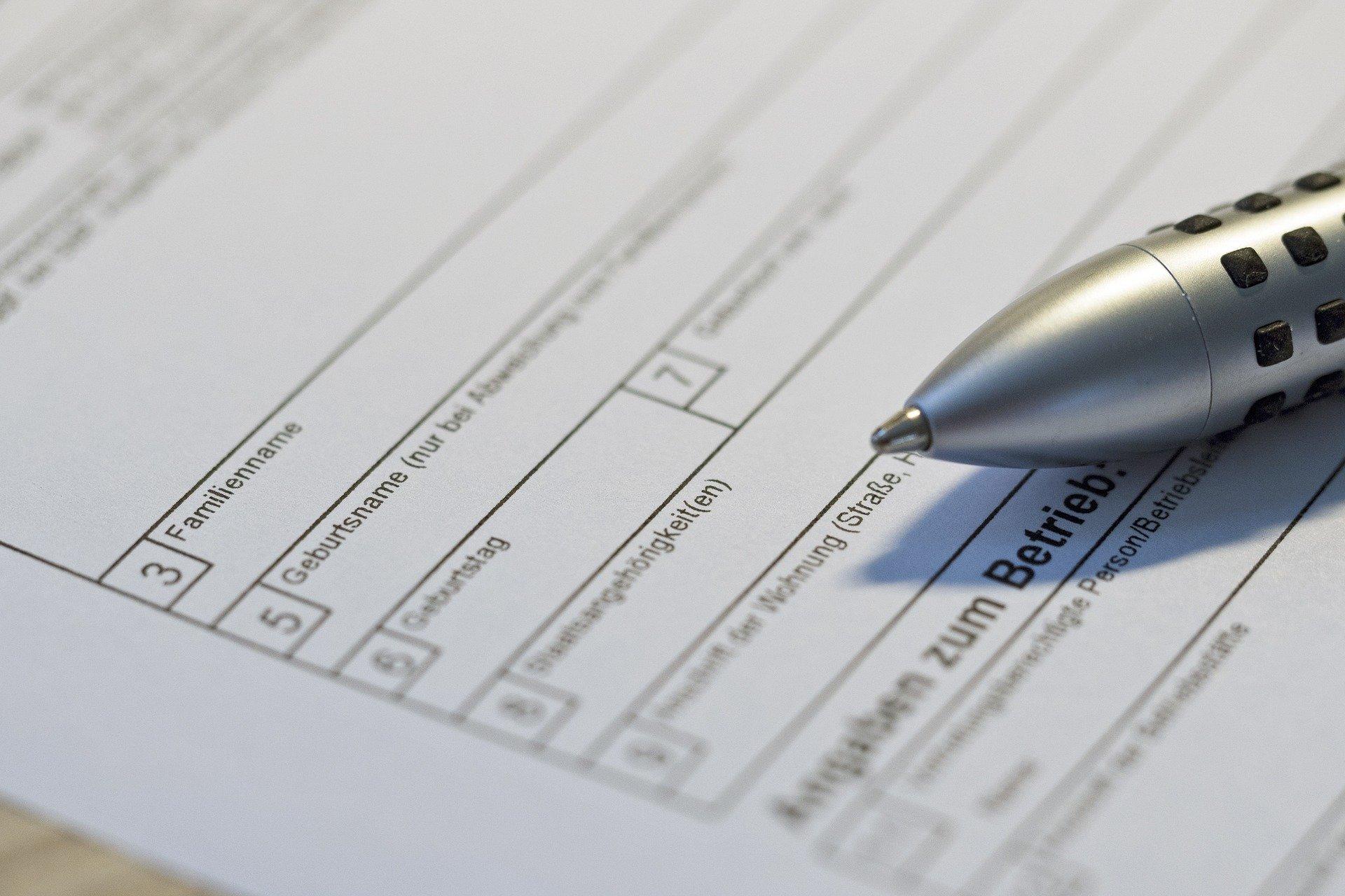Das Foto zeigt ein Formular. Darauf liegt ein Kugelschreiber.